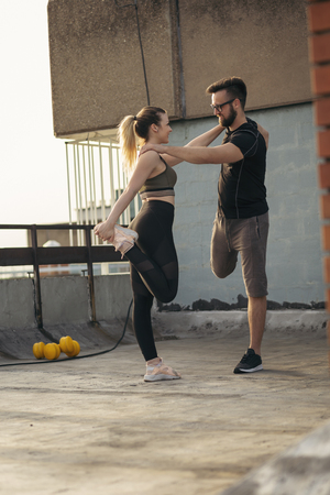 Young couple on a building rooftop terrace stretching before workout; urban skyline in the background