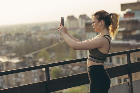 Beautiful young woman taking a workout break, standing on a building rooftop terrace, taking urban skyline photos and enjoying sunset over the city