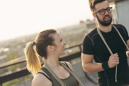 Couple standing on a building rooftop terrace, getting ready for exercising with ropes. Focus on the girl