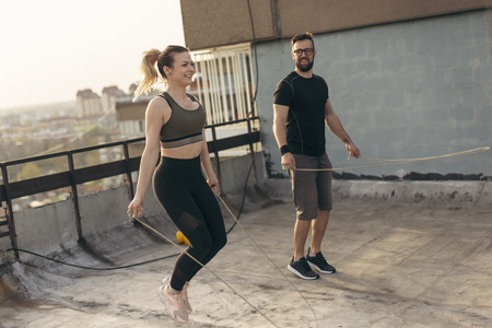 Couple exercising on a building rooftop terrace, jumping ropes. Focus on the girl Imagens
