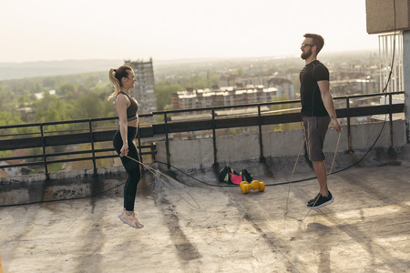 Couple exercising on a building rooftop terrace, jumping ropes; urban skyline in the background