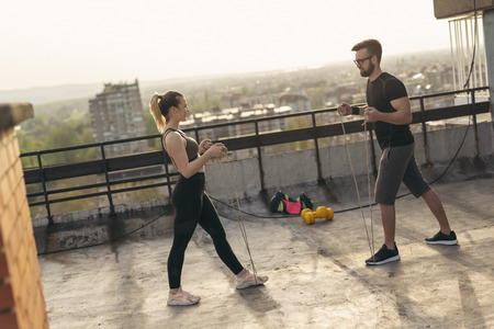 Couple standing on a building rooftop terrace, exercising with ropes. Urban skyline in the background; focus on the girl