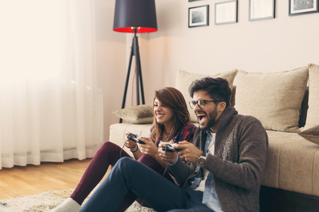 Couple in love enjoying their free time, sitting on the living room floor, playing video games and having fun. Focus on the woman