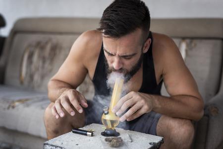 Pote que fuma del hombre joven usando bong; Hombre inhalando vapor de marihuana de un bong Foto de archivo