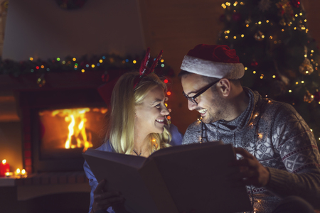 Couple in love enjoying winter holidays at home, sitting by the fireplace and looking through an old photo album on Christmas night. Focus on the girl