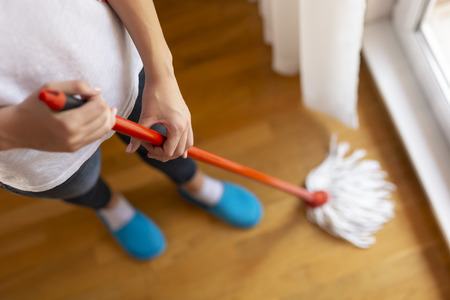 High angle view of woman holding a floor wiper and wiping floor, keeping the daily home hygiene. Selective focus on the hand