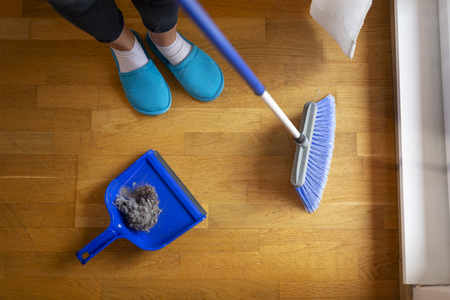 High angle view of female hands holding a broom and sweeping floor, collecting dust onto a dustpan Stockfoto