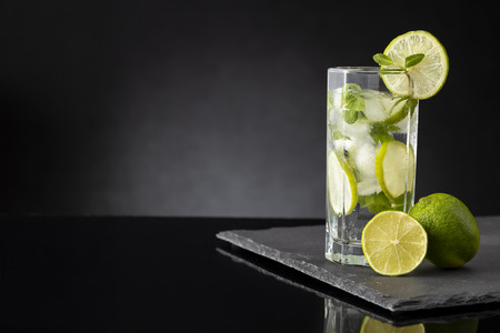 Mojito cocktail with lots of ice, white rum, lemon juice and tonic, decorated with lime slices and mint leaves on a black stone tray