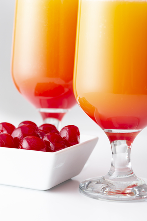 Two cold tequila sunrise cocktails with tequila, pomegranate juice and orange juice decorated with slices of orange and maraschino cherries. Selective focus on the maraschino cherries