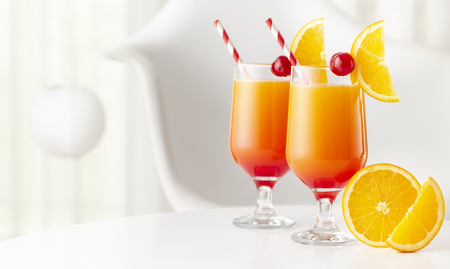 Two cold tequila sunrise cocktails with tequila, pomegranate juice and orange juice decorated with slices of orange and maraschino cherries. Focus on the closer glass