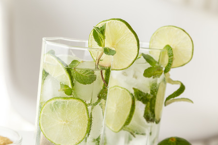 Two mojito cocktails with lots of ice, white rum, lemon juice and tonic, decorated with lime slices and mint leaves
