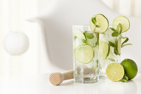 Two mojito cocktails with lots of ice, white rum, lemon juice and tonic, decorated with lime slices and mint leaves on a modern white table.