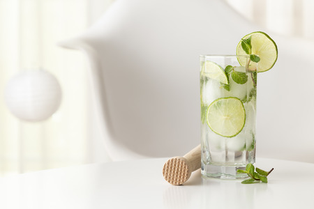 Mojito cocktail with lots of ice, white rum, lemon juice and tonic, decorated with lime slices and mint leaves on a modern white table Stockfoto