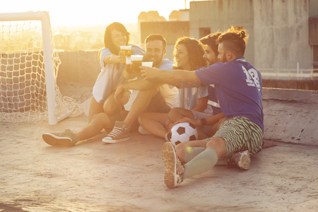 Group of young people sitting on a building rooftop, wearing jerseys, resting after a football match, drinking beer and making a toast. Focus on the guys on the right