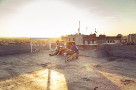 Group of young people sitting on a building rooftop, wearing jerseys, resting after a football match, drinking beer and making a toast Stockfoto