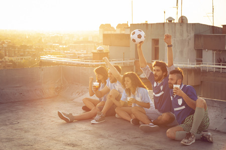 Group of young friends watching a football match on a building rooftop, cheering and drinking beer Stockfoto