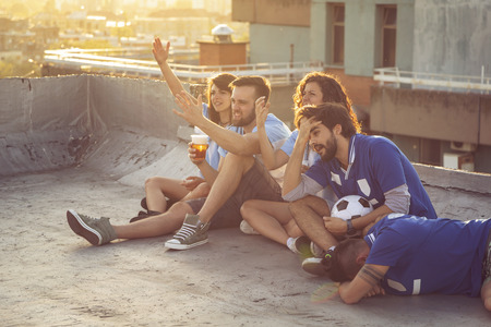 Group of young friends watching a football match on a building rooftop, cheering and drinking beer. Focus on the couple in the middle