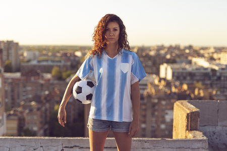 Young woman wearing a football jersey standing on a building rooftop, holding a ball and watching a sunset over the city.