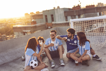 Group of young people sitting on a building rooftop, wearing jerseys, taking a break from a football match, enjoying sunset over the city. Focus on the guys in the middle