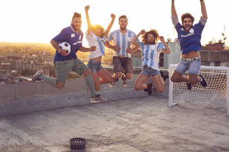 Group of young friends having fun on a building rooftop after a football match; jumping, all caught in the air with the cityscape and urban sunset in the background