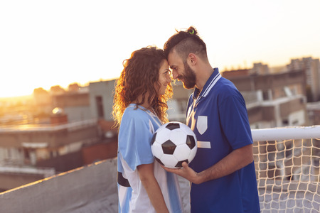 Couple in love wearing football jerseys, standing on a building rooftop after a match and enjoying a beautiful sunset over the city Stockfoto