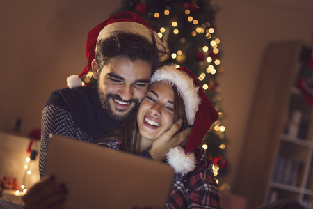 Couple in love sitting next to a Christmas tree, wearing Santa hats and having fun looking at old photos on a tablet computer