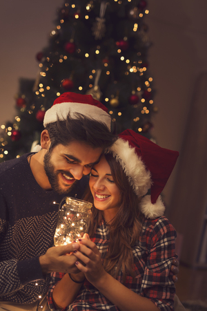 Beautiful couple in love sitting on the living room floor next to a Christmas tree, holding a jar with Christmas lights Stockfoto