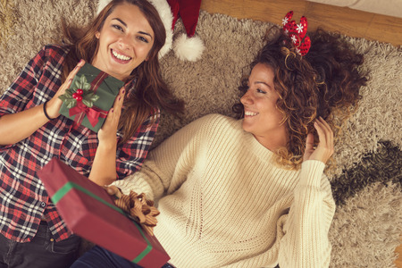 Top view of two beautiful women lying on a carpet on a living room floor, holding nicely wrapped Christmas present boxes. Focus on the girl on the right Stockfoto