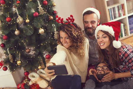 Group of young friends sitting on the floor next to a nicely decorated Christmas tree, wearing Santa hats and taking a selfie. Focus on the girl with the phone