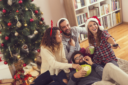 Group of young friends sitting on the floor next to a Christmas tree, eating popcorn and watching a Christmas movie Stockfoto