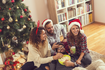 Group of young friends sitting on the floor next to a Christmas tree, eating popcorn and watching a Christmas movie. Focus on the girls
