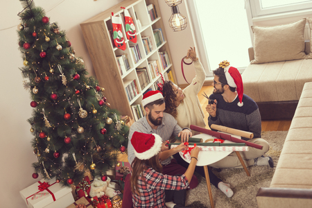 Group of young friends sitting next to the Christmas tree, wrapping Christmas presents and having fun