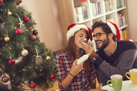 Couple in love sitting by the nicely decorated Christmas tree, drinking coffee, decorating and eating gingerbread Christmas cookies and having fun Stockfoto