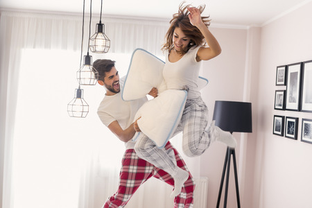 Happy loving couple having fun while having a pillow fight and jumping on bed Stockfoto