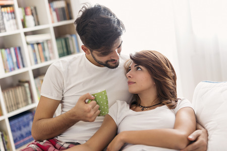 Loving couple cuddling and drinking coffee after waking up in bed Stockfoto