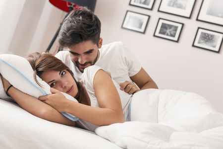 Young couple lying on the bed, having an argument Stockfoto