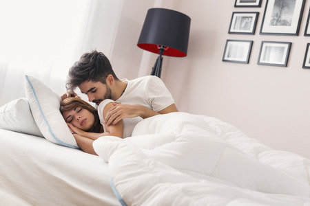 Couple in love lying in bed, hugging and kissing after waking up in the morning Stockfoto