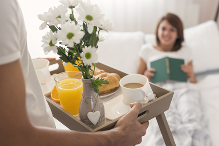 Happy and surprised young woman lying in bed in the morning while her husband is bringing her breakfast and flowers on a tray. Selective focus on the orange juice Stockfoto