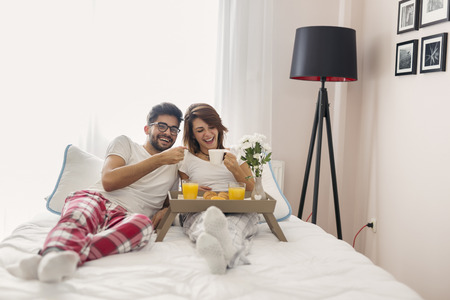 Happy couple in love lying in bed, having breakfast and enjoying their time together, drinking their morning coffee
