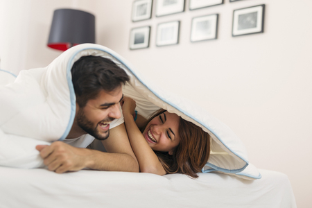 Couple in love lying under the sheets, peeking and laughing, enjoying the freedom of weekend mornings Stockfoto