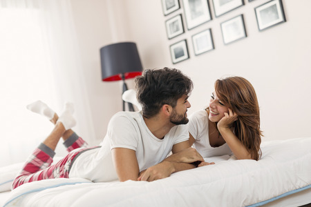 Young couple in love lying in bed after waking up, cuddling and having fun