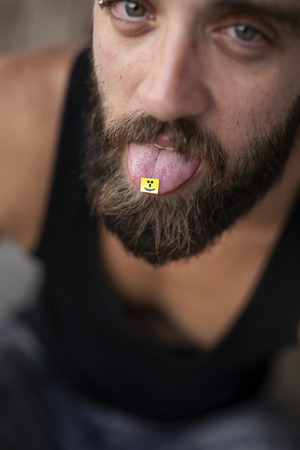 Young man taking LSD; LSD card on a mans tongue. Focus on the LSD stamp