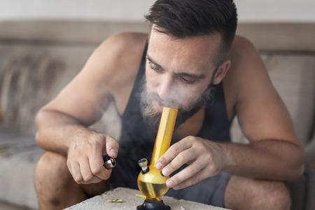 Young man smoking pot using bong; man inhaling marijuana vapor from a bong Imagens