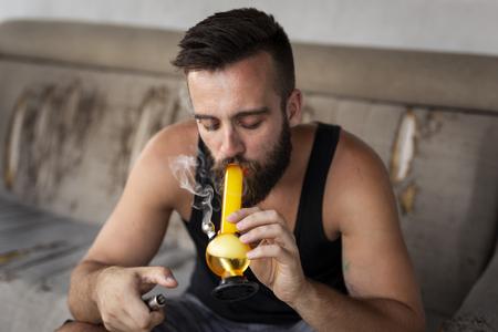 Young man smoking pot using bong; man inhaling marijuana vapor from a bong Reklamní fotografie