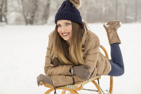 Attractive young woman lying on a sleigh in the snow, enjoying a beautiful winter day in nature