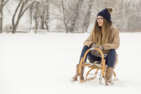 Beautiful young woman wearing warm winter clothes and sitting on a sleight on a snowy winter day Stock Photo