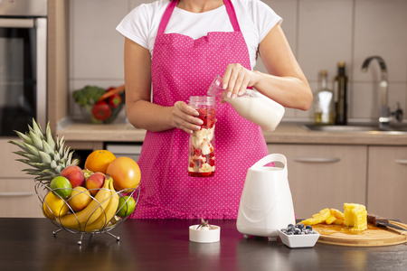 Detail of a woman pouring milk over the fruits into a blender bowl and making fresh raspberry, banana, milk and honey smoothie for breakfast Reklamní fotografie