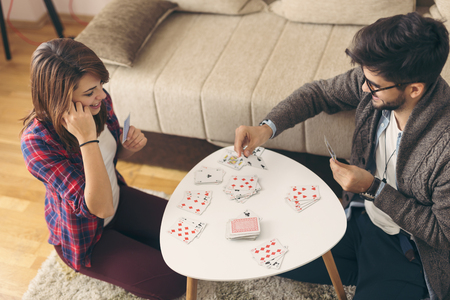 High angle view of couple sitting on the living room floor next to a coffee table and having fun playing cards. Focus on the woman
