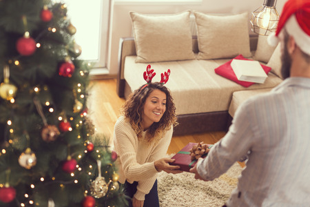 Beautiful young couple in love standing next to a nicely decorated Christmas tree, exchanging presents on Christmas morning