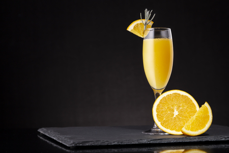 Mimosa cocktail in a champagne glass with orange juice and sparkling wine decorated with lavender leaves and orange slices